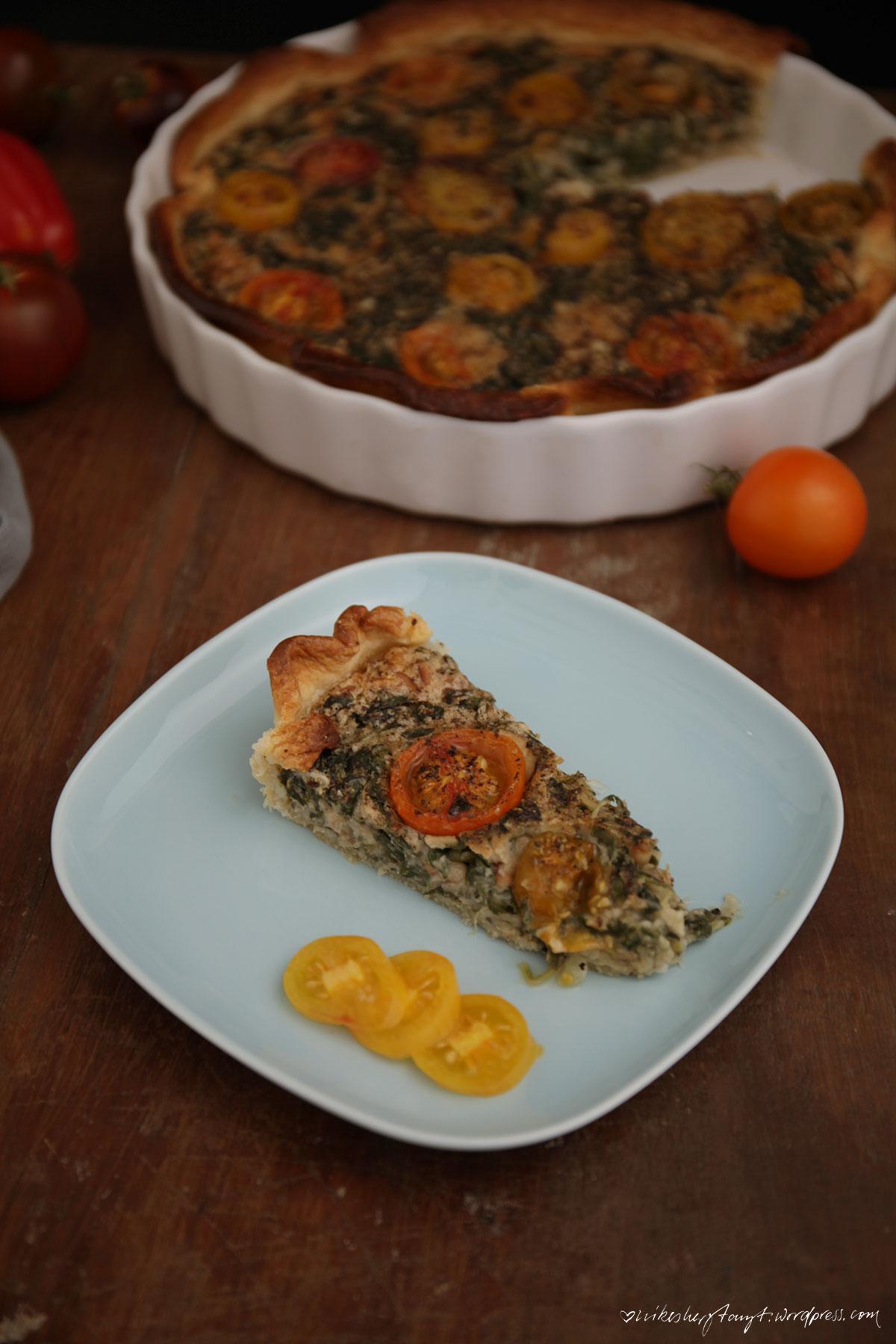 vegane spinat quiche mit pinienkernen und bunten tomaten in weißer form auf holz, nikesherztanzt